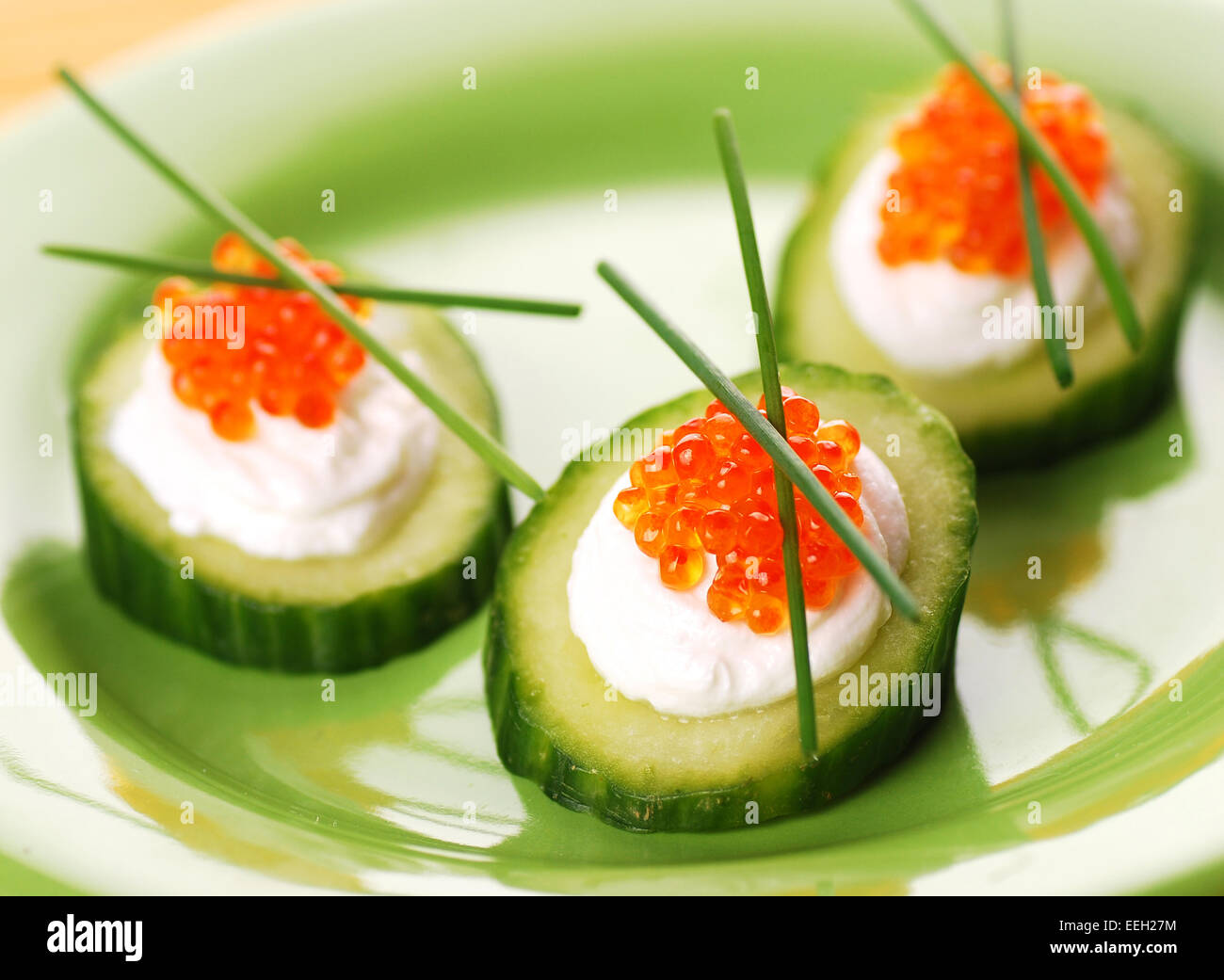 Appetizers with red caviar and a cucumber - Stock Image