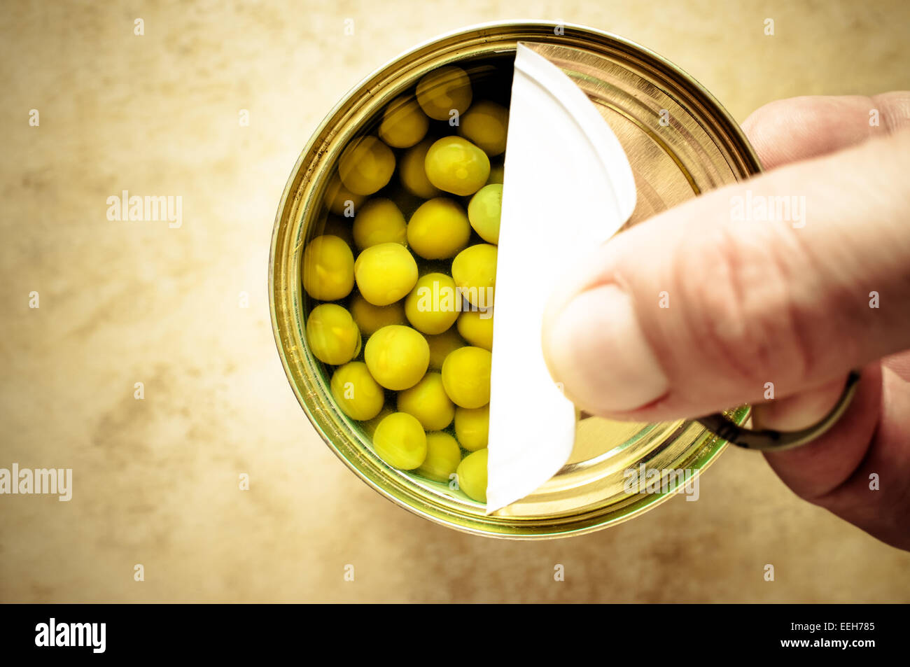Man opens canned peas hand - Stock Image