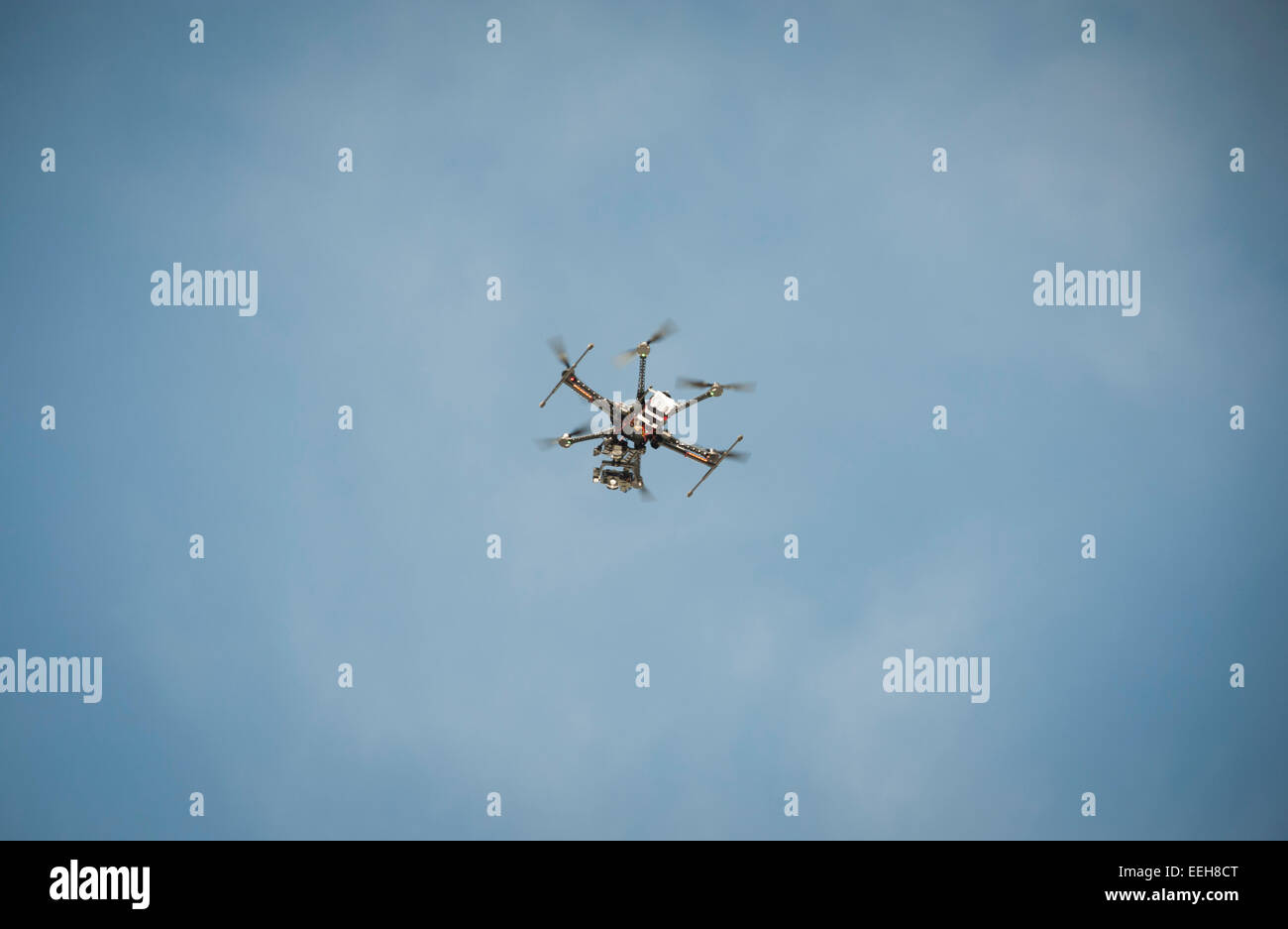 A civil Unmanned Aerial Vehicle (UAV) / multicopter drone used for aerial surveillance is flying in the air - Stock Image