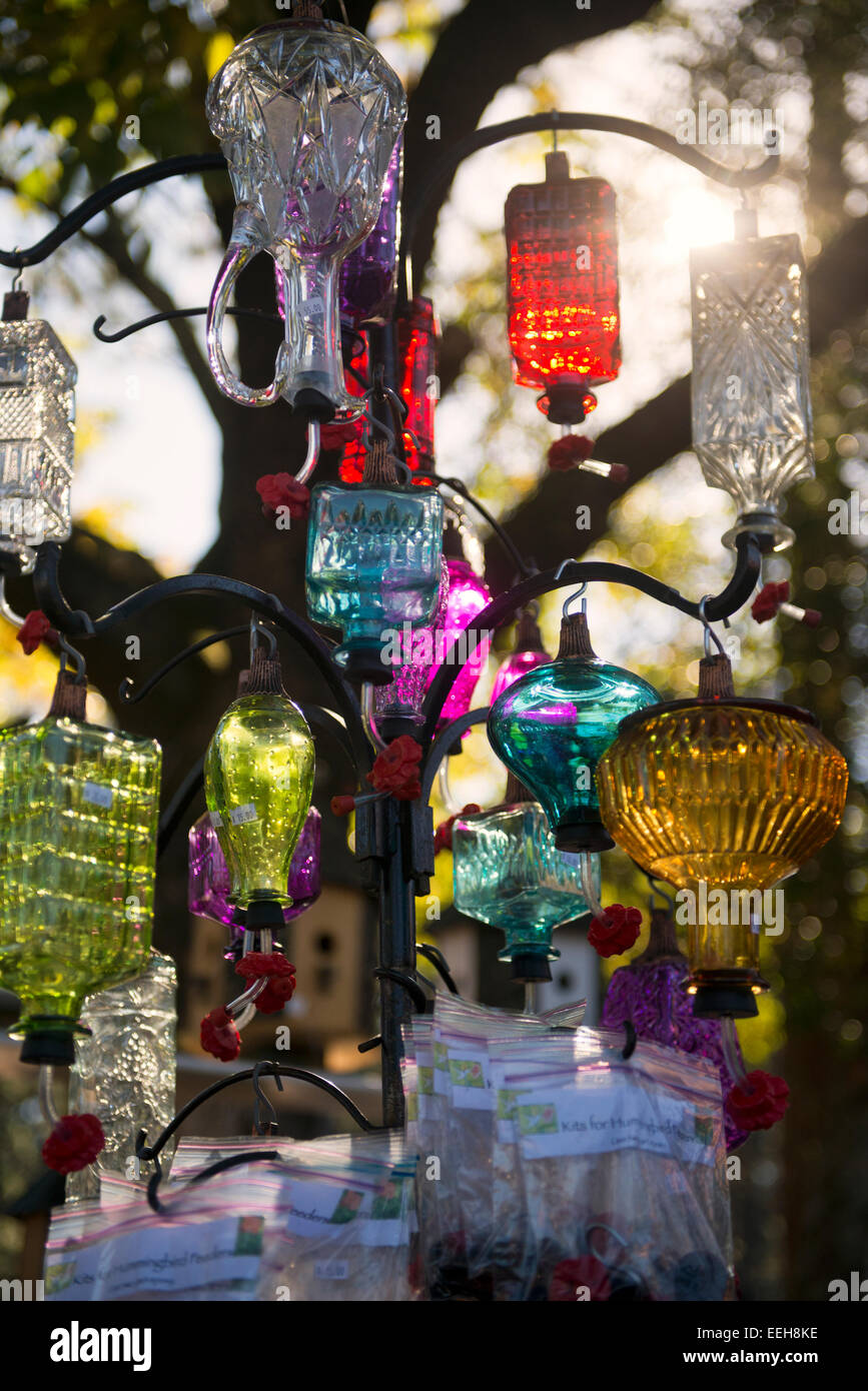 Artistic crafty humming bird feeders reflecting glaring sunlight - Stock Image