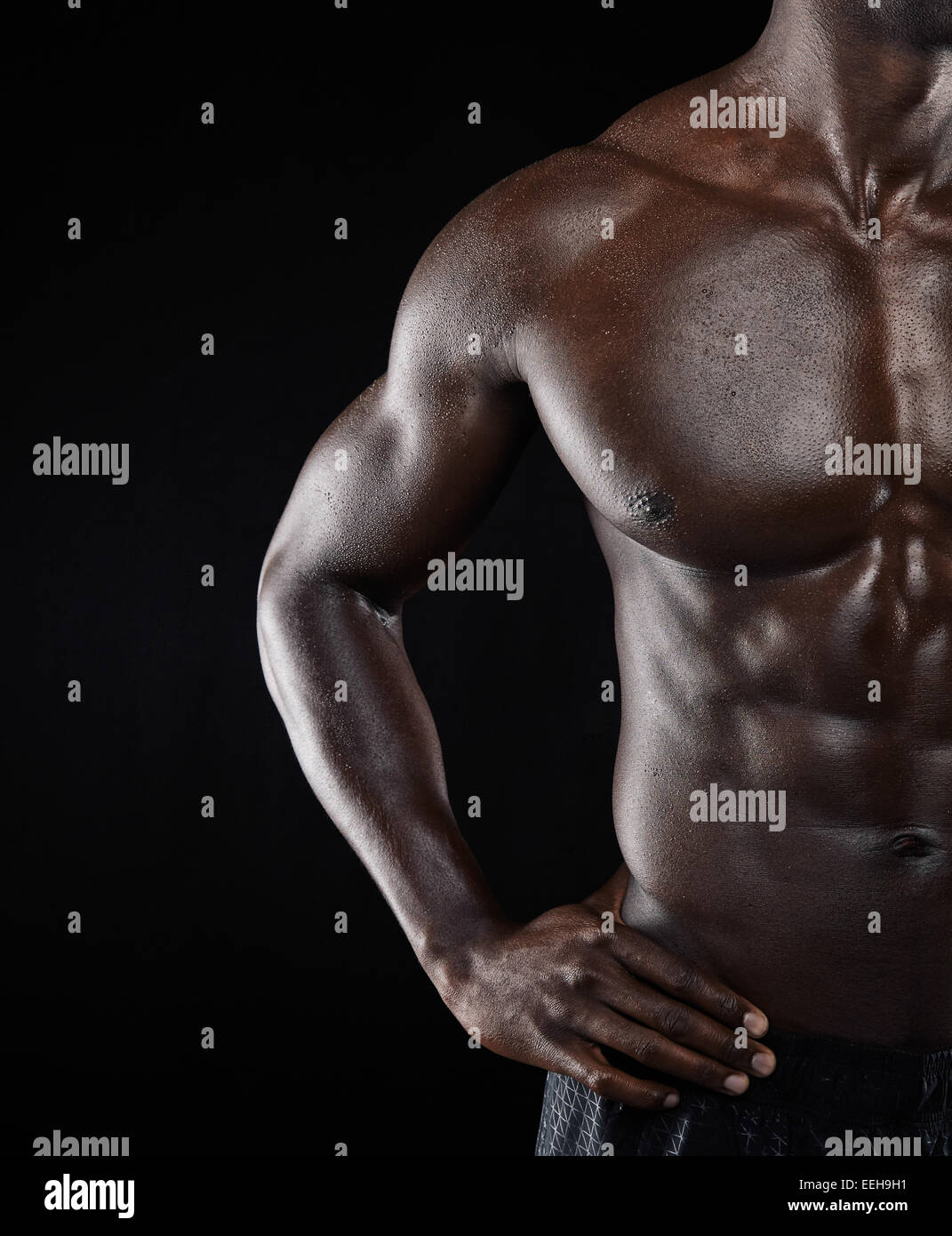 Close-up shot of young African muscular man body against black background. Shirtless male model with muscular build. - Stock Image