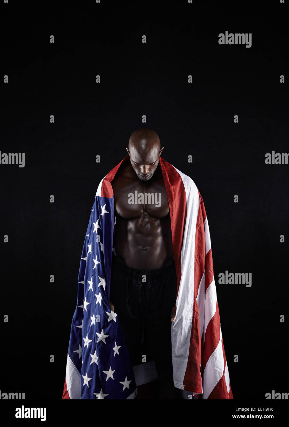 Shirtless muscular man with American flag on black background. Olympics athlete with USA flag looking down. - Stock Image