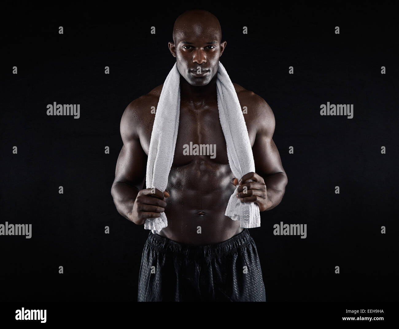 Shirtless muscular man holding towel looking at camera on black background. Fit young African man after workout. - Stock Image