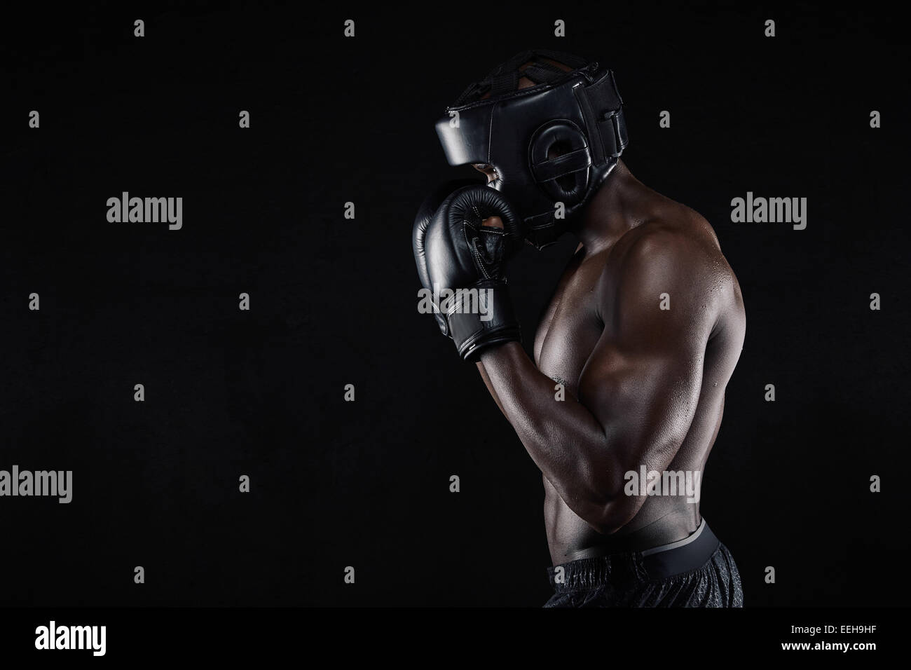 Side view of a young male boxer in a fighting stance on black background. African male boxer blocking his face with - Stock Image