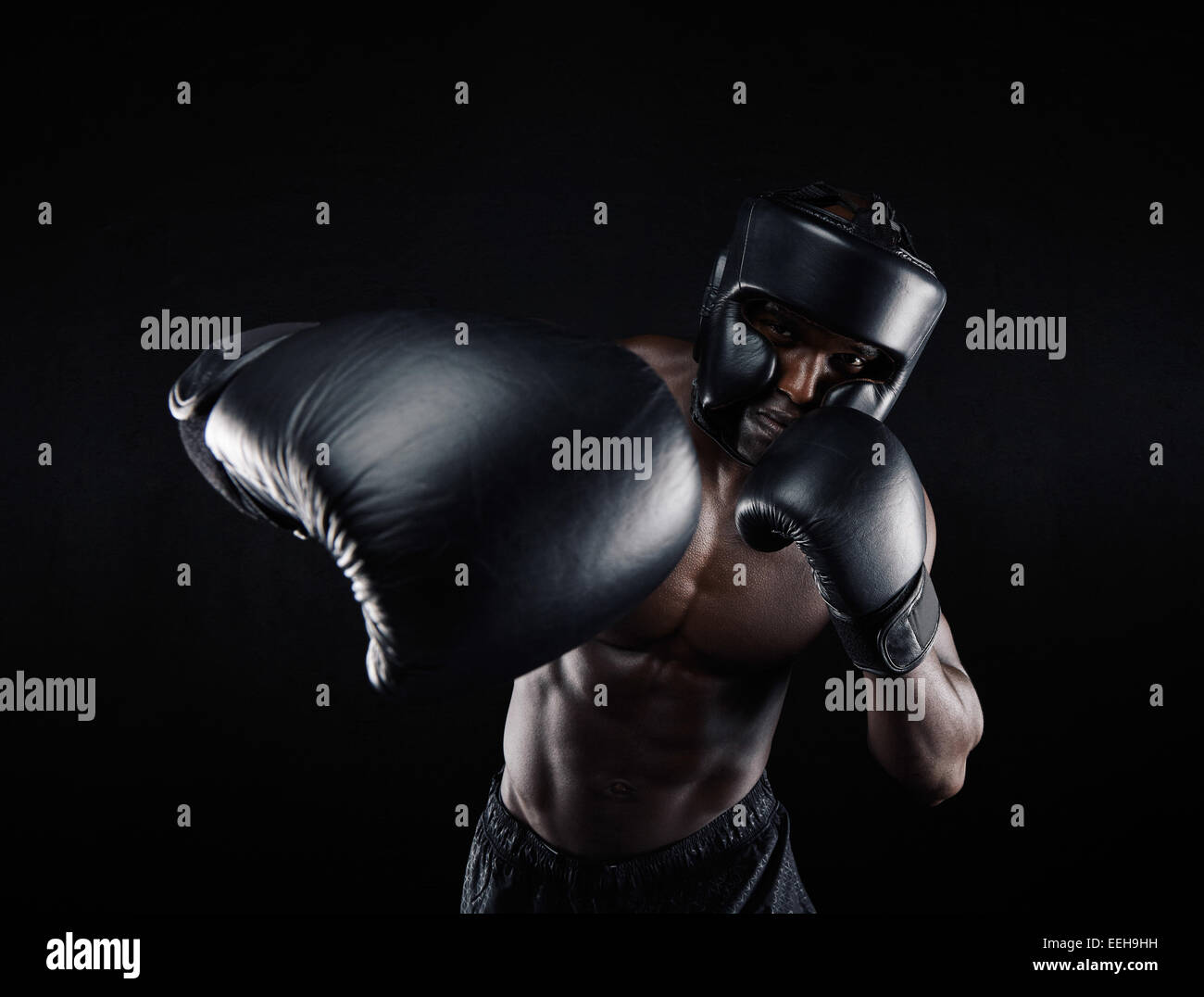 Portrait of African male practicing boxing against black background. Male boxer throwing a punch in front. Young - Stock Image