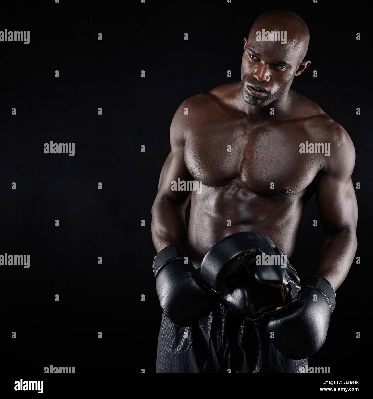 Portrait of sporty young man with muscular body holding boxing helmet. African male boxer against black background - Stock Image