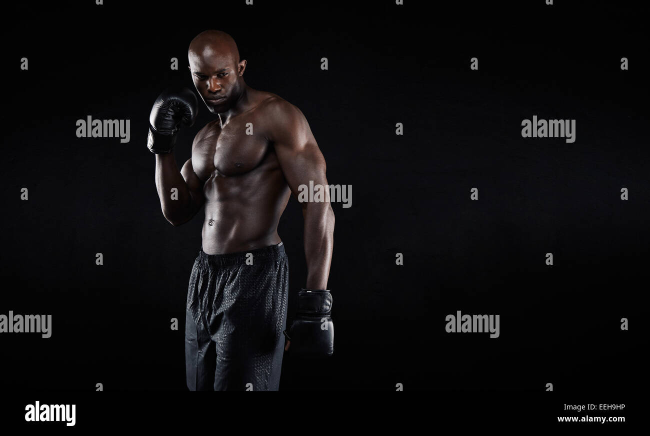Professional fighter portrait on black background. Shirtless muscular african boxer looking at copyspace. - Stock Image