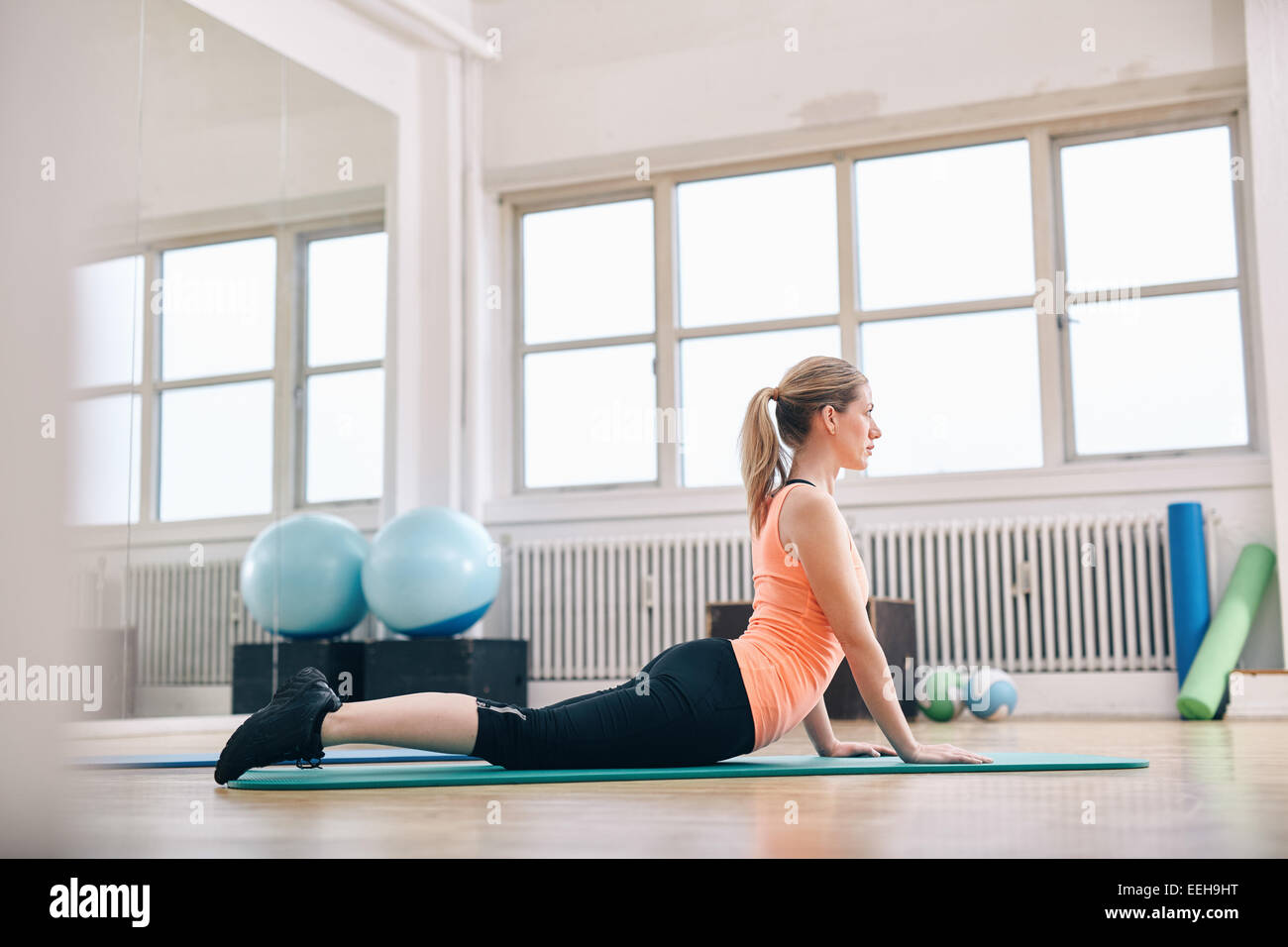 Woman doing core stretch on fitness mat. Attractive young woman doing yoga at gym. - Stock Image