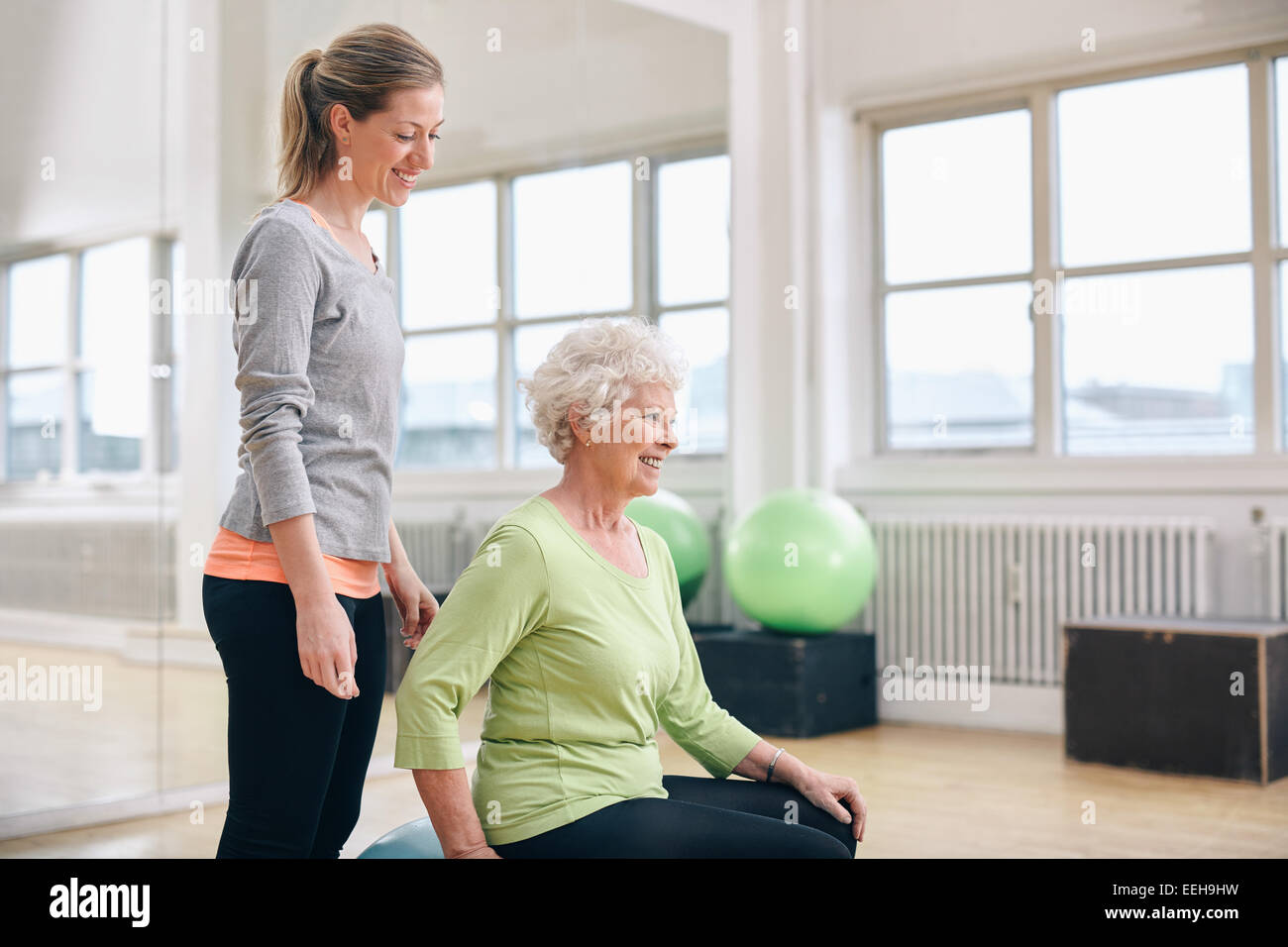 Portrait of female instructor assisting senior woman exercising in gym. Two fitness woman at health club exercising. - Stock Image