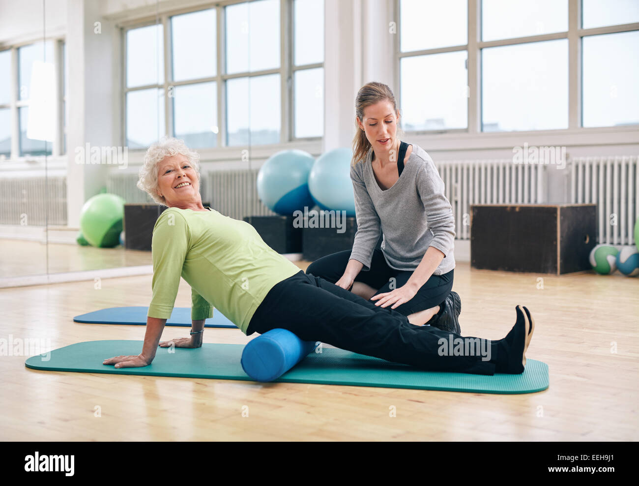 Senior woman doing pilates on the floor with foam roller. Elder woman exercising being assisted by personal trainer - Stock Image