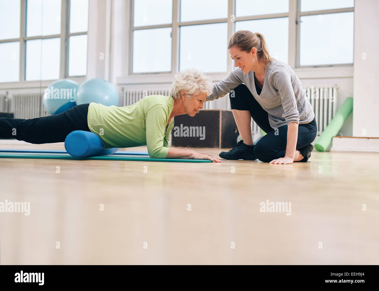 Senior woman exercising with a foam roller being assisted by personal instructor at gym. Physical therapist helping - Stock Image