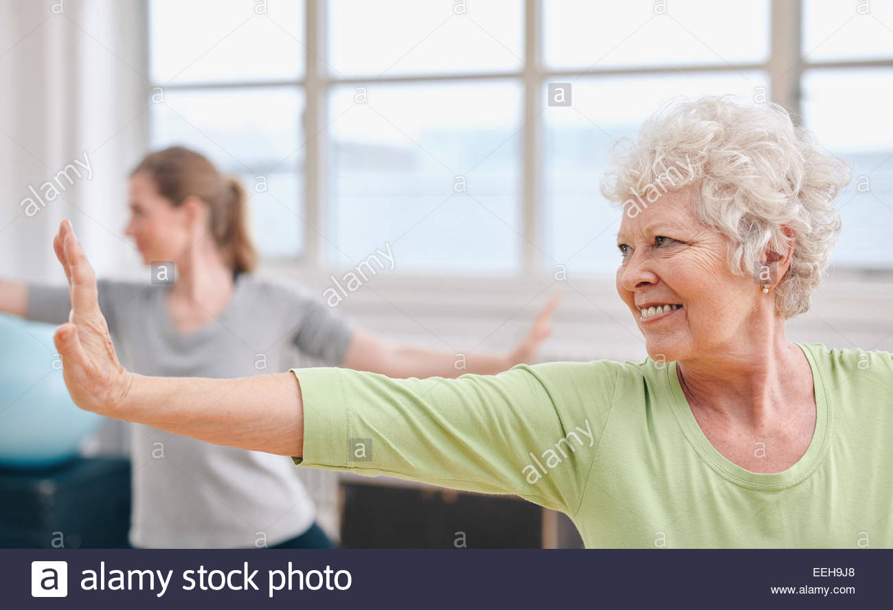 Portrait of happy senior woman practicing yoga at gym class. Elderly woman stretching her arms . - Stock Image