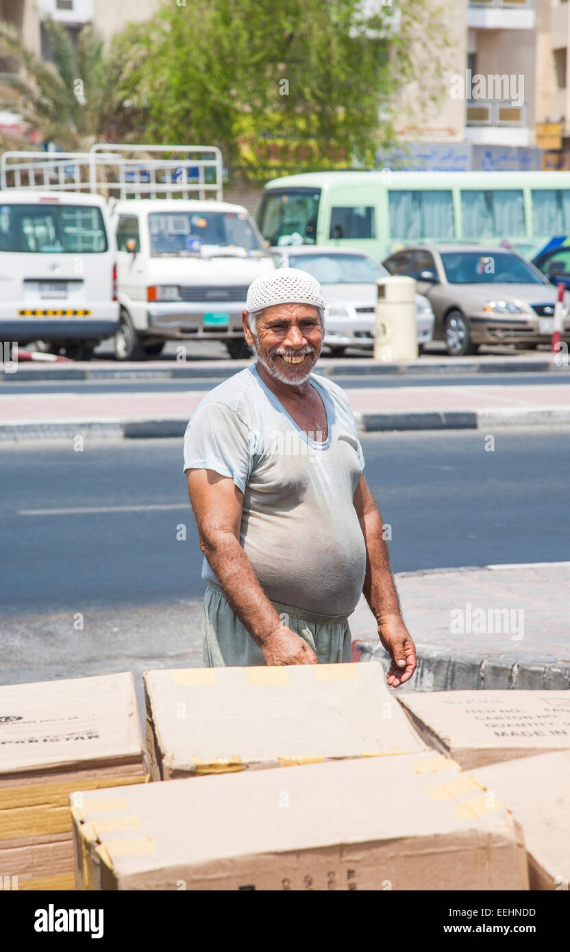 Typical manual dock worker: Smiling happy local paunchy dock labourer wearing a dirty t-shirt working loading boxes - Stock Image