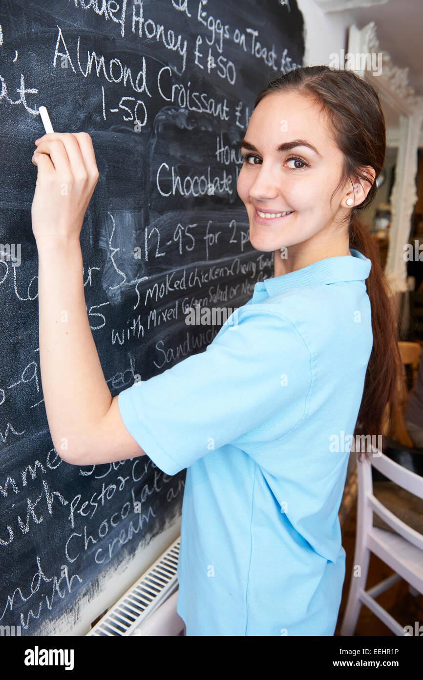 Waitress In Restaurant Writing Menu On Blackboard - Stock Image