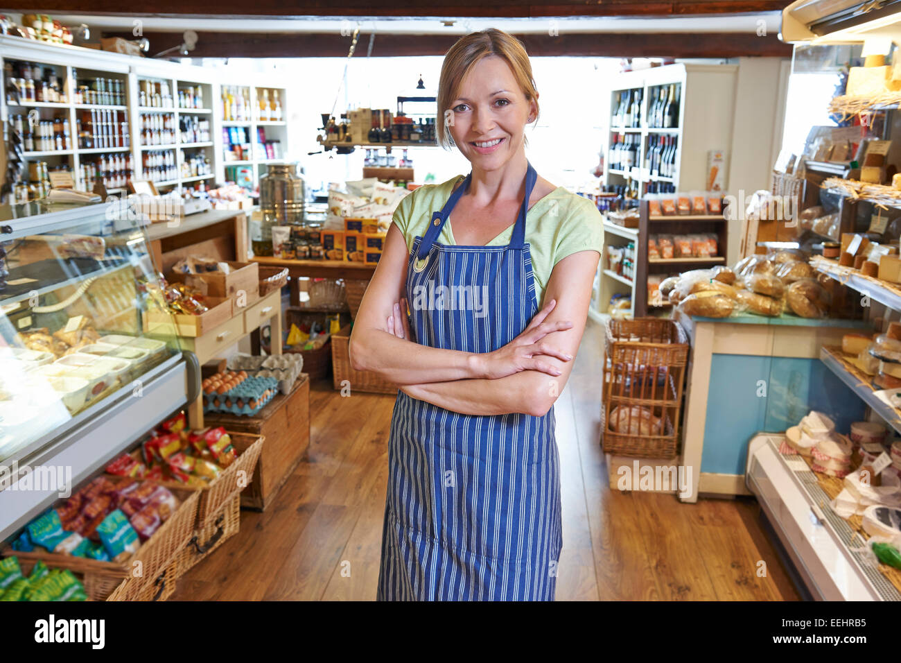 Owner Of Delicatessen Standing In Shop - Stock Image