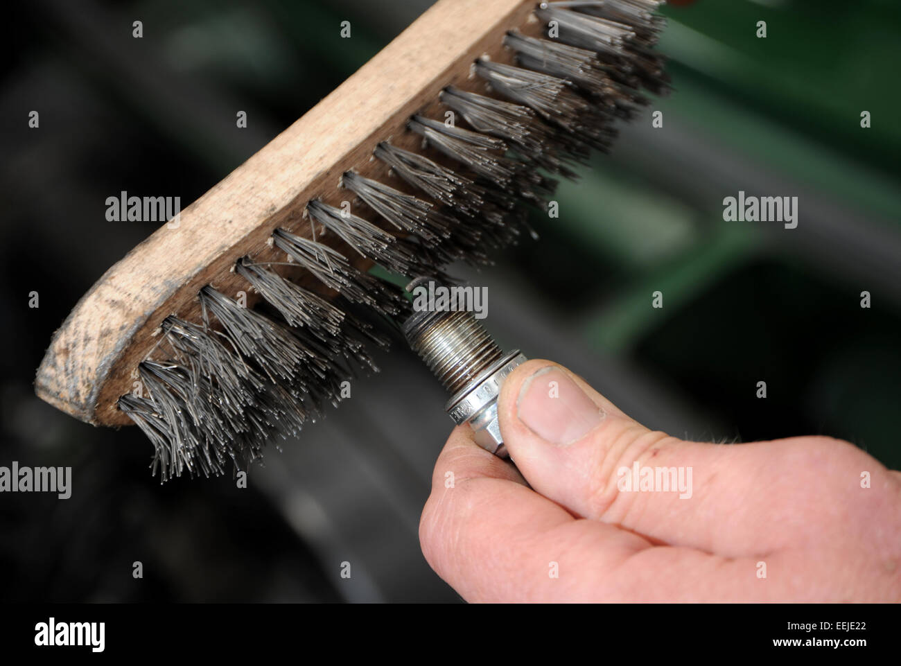 How To Clean Spark Plugs >> Cleaning A Car Engine Spark Plug With A Wire Brush Stock Photo