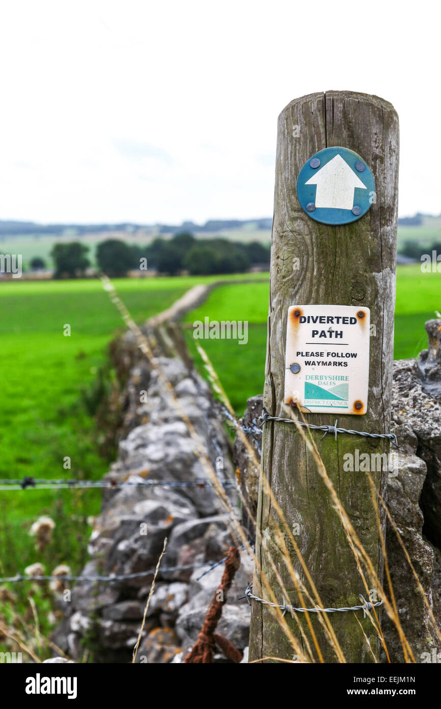 A sign in a field with dry stone walls saying diverted path please follow waymarkers Derbyshire Dales District Council - Stock Image