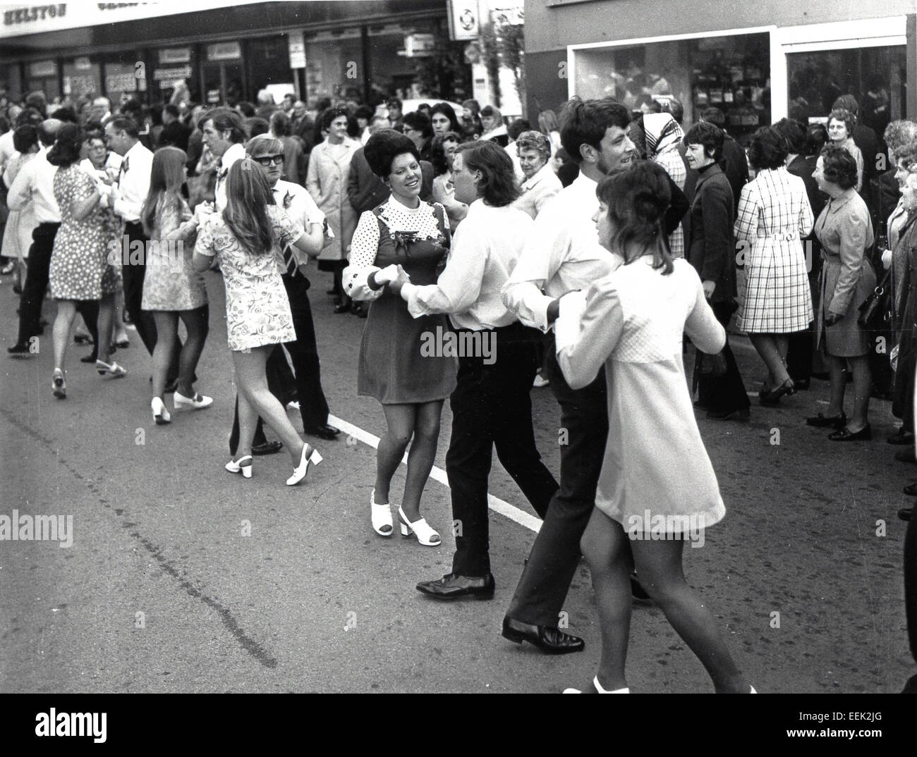 1960s historical, shoppers watching men and women dancing together in the street, with girls wearing flower patterned - Stock Image