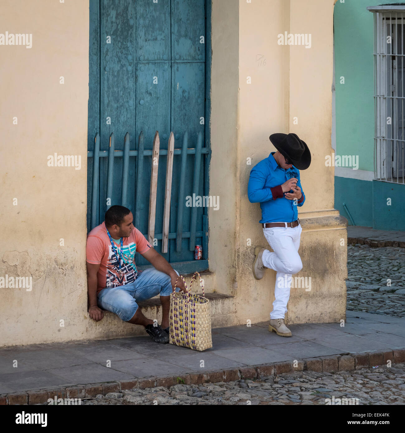 Two men on a street corner in Trinidad, Cuba. One seated and one standing with hat on. Stock Photo