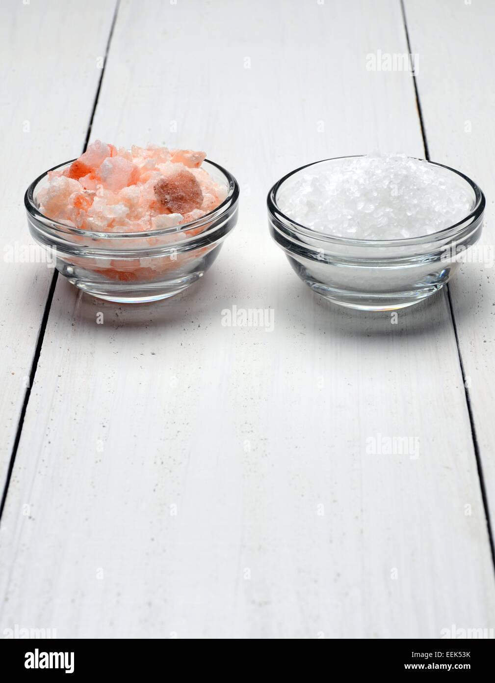 Himalayan pink salt, and sea salt on a wooden table - Stock Image