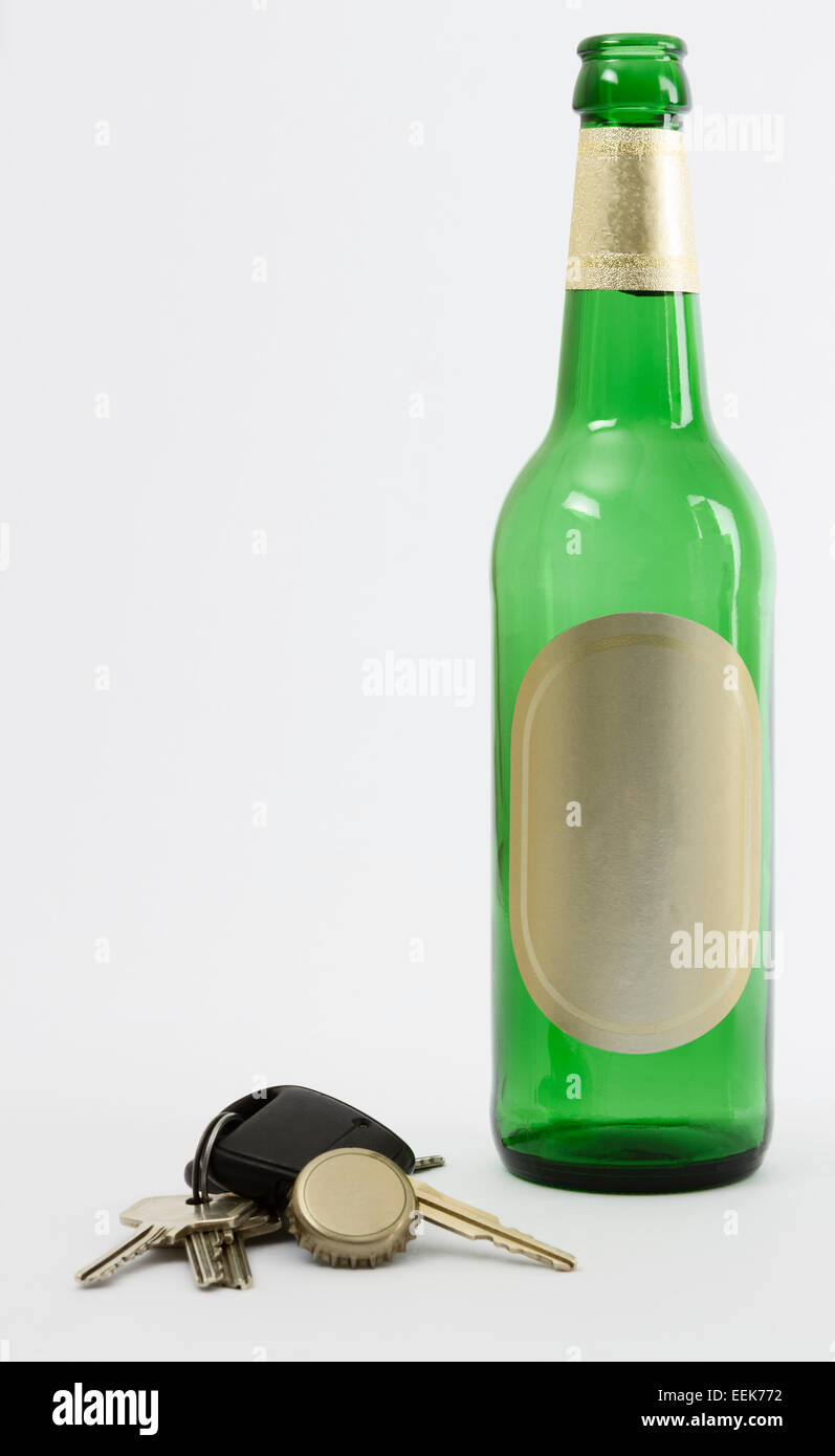 empty beer bottle with car key and crown cork isolated in grey background. - Stock Image