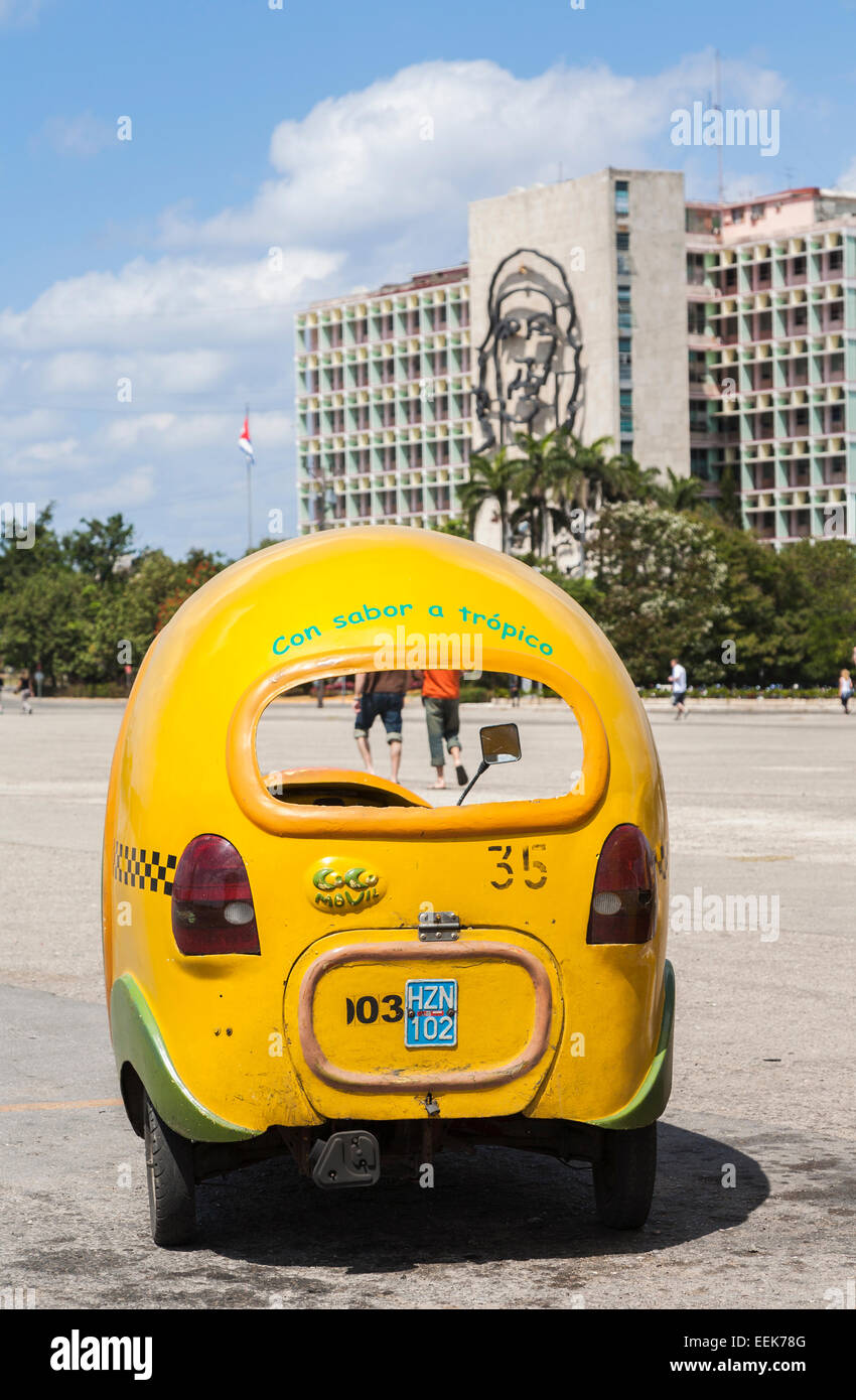 Yellow coco taxi cab parked at the Ministry of Interior building with image of Che Guevara in Plaza de la Revolución, - Stock Image