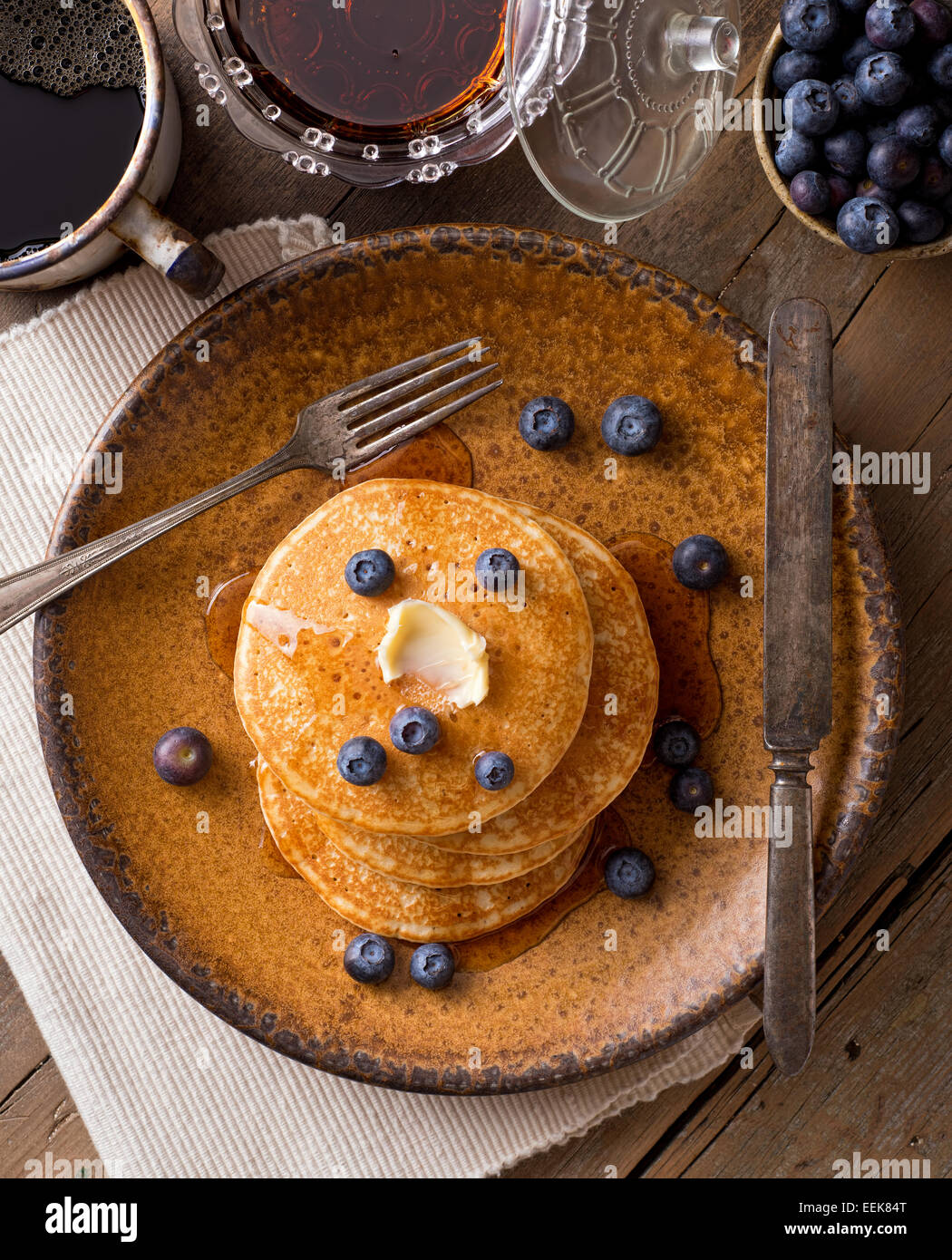 Pancakes with blueberries and maple syrup on a rustic tabletop. - Stock Image