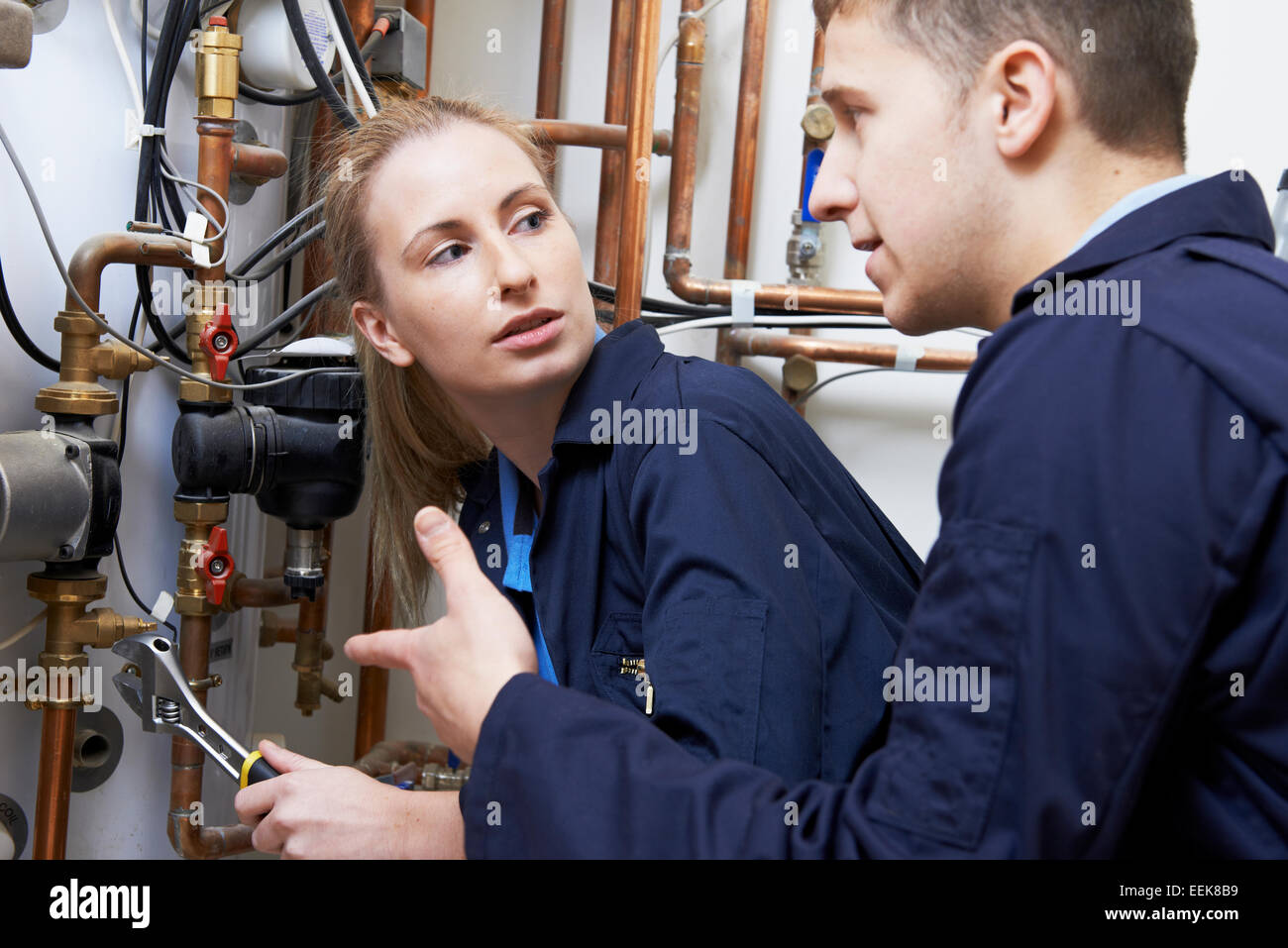 Female Trainee Plumber Working On Central Heating Boiler - Stock Image
