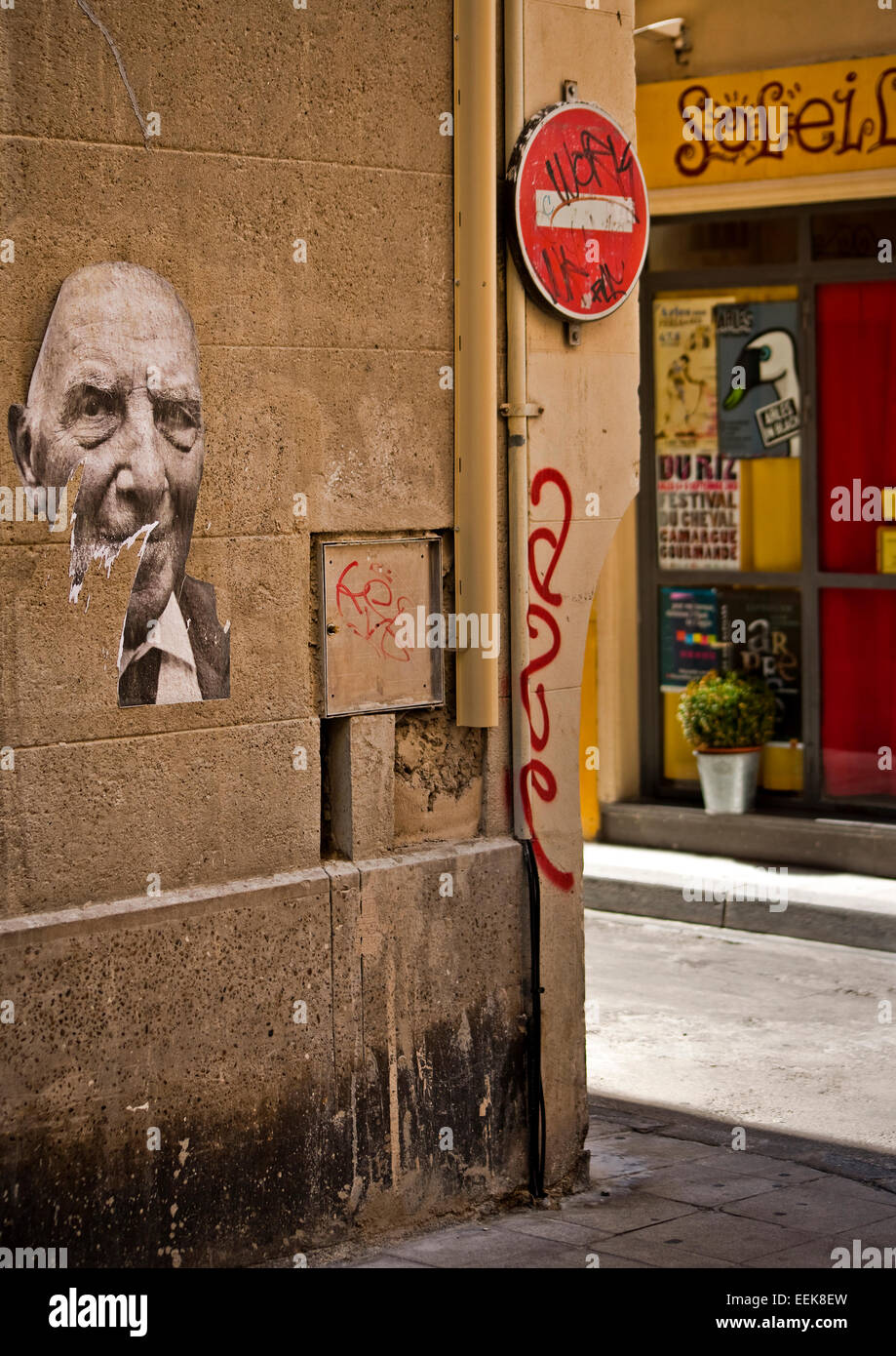 French ripped paper posters of mans face on wall, shadows and sunlight no entry traffic sign - Stock Image