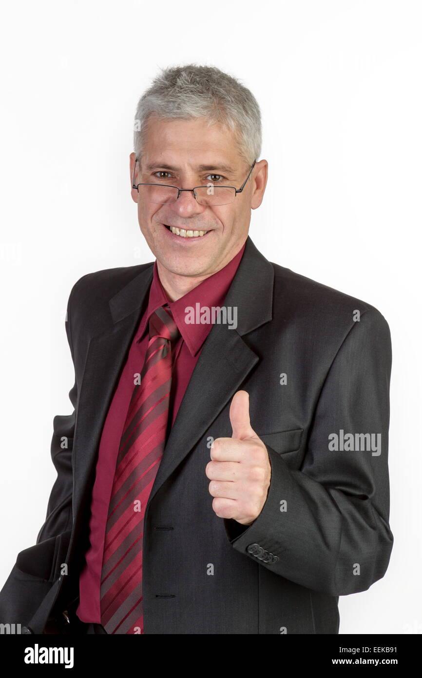 Geschäftsmann hält den Daumen hoch, Businessman holds up thumb - Stock Image