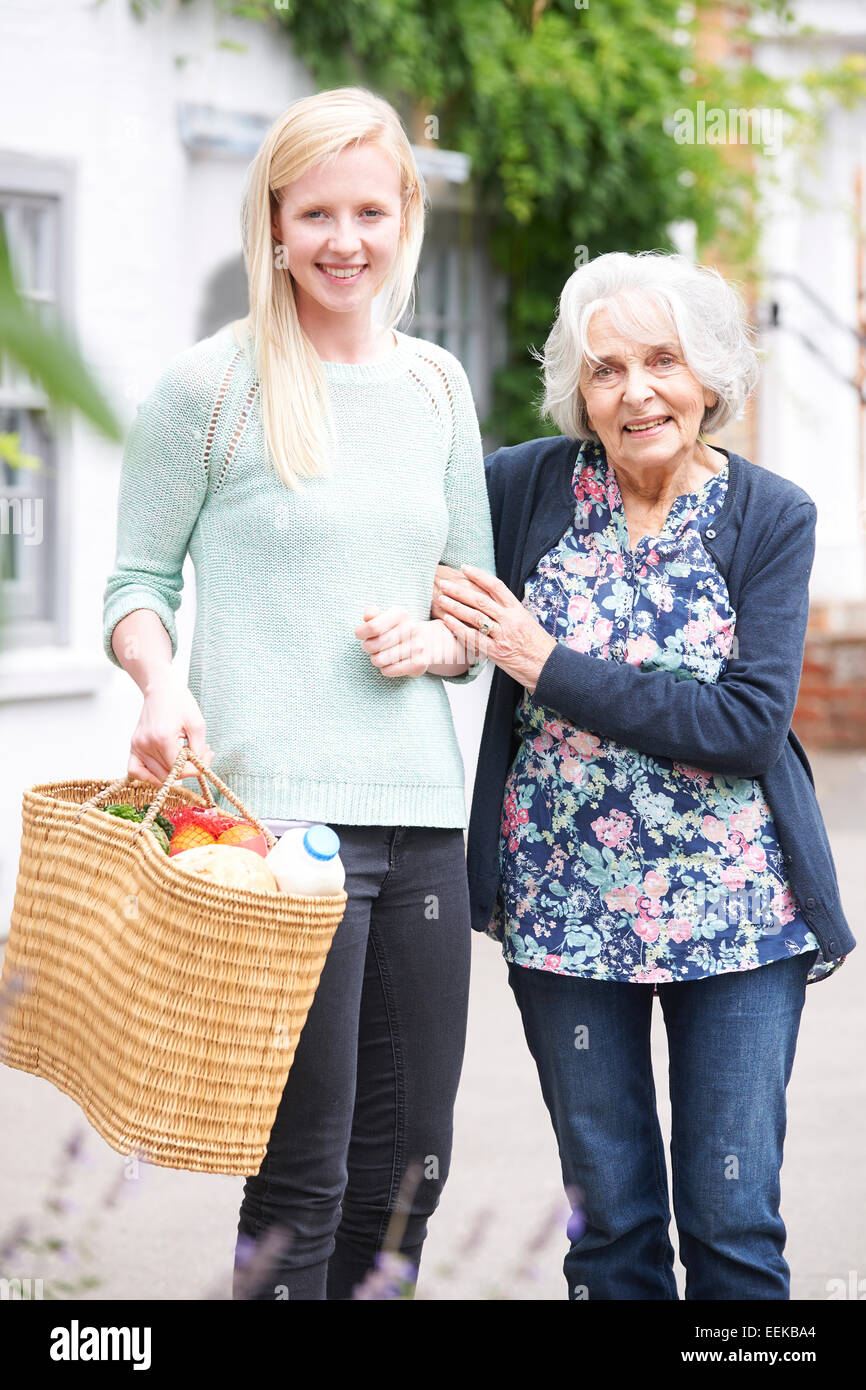 Teenage Girl Helping Senior Woman To Carry Shopping - Stock Image