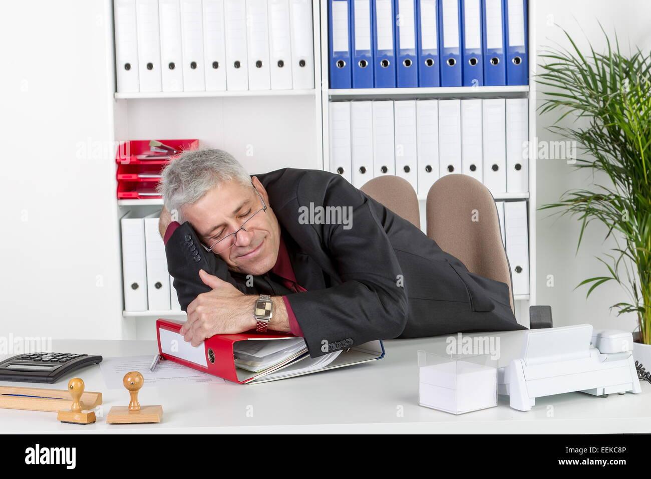 Mann mittleren Alters sitzt im Büro, liegt auf Akternordnern und schläft, Middle-aged man, sitting in - Stock Image