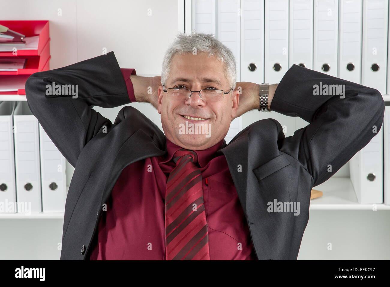 Mann mittleren Alters sitzt im Büro und relext, Middle-aged man sitting in an office, relaxing - Stock Image
