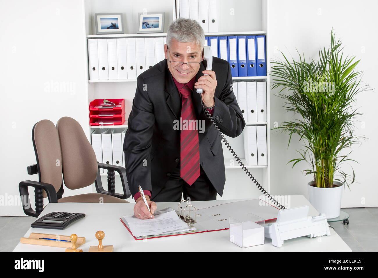 Mann mittleren Alters im Büro steht am Schreibtisch und telefoniert, Middle-aged businessman in his office, - Stock Image