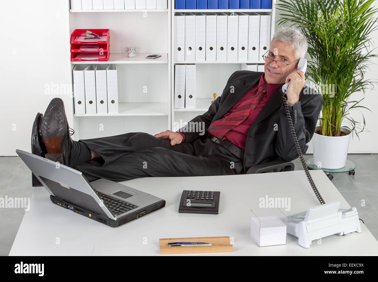 Mann mittleren Alters sitzt im Büro hat lässig die Beine auf dem Schreibtisch und telefoniert, Middle - Stock Image