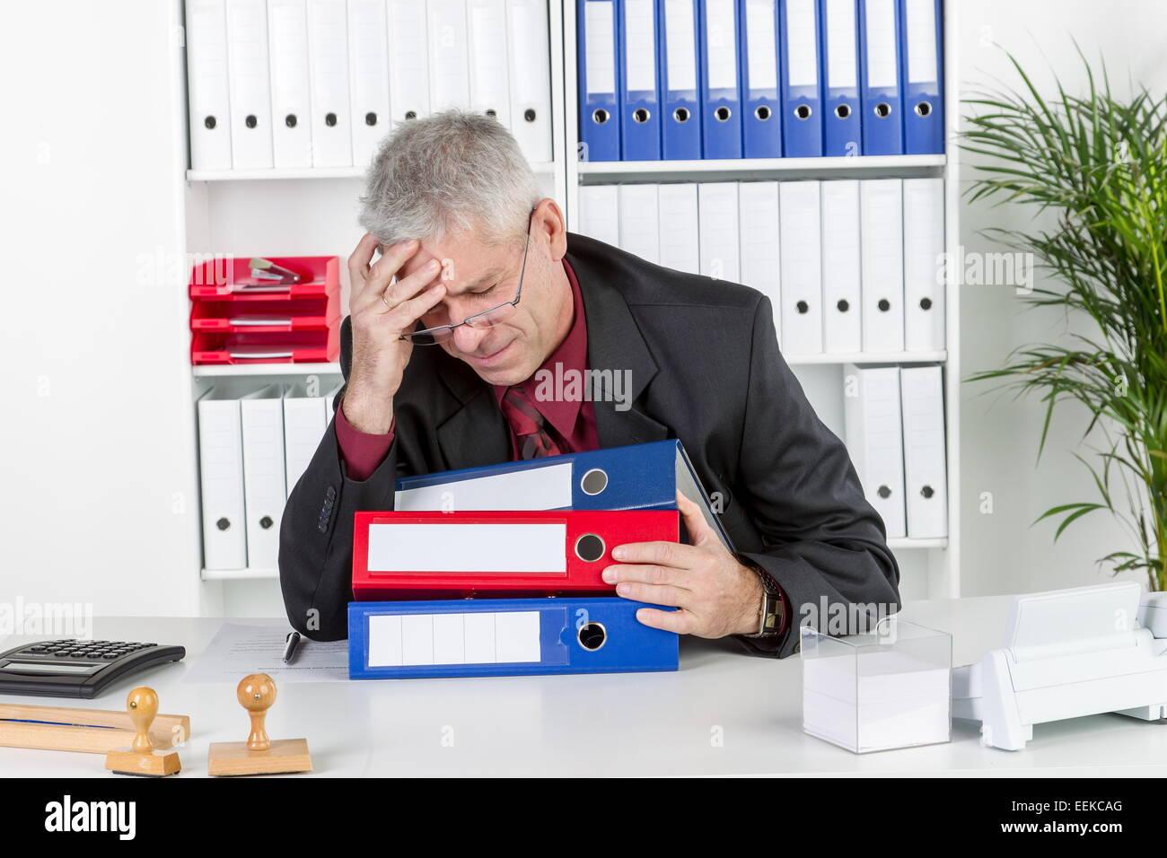 Mann mittleren Alters sitzt im Büro, hält sich den Kopf, hat Kopfschmerzen, Middle-aged man with a headache, sits in his office, Stock Photo