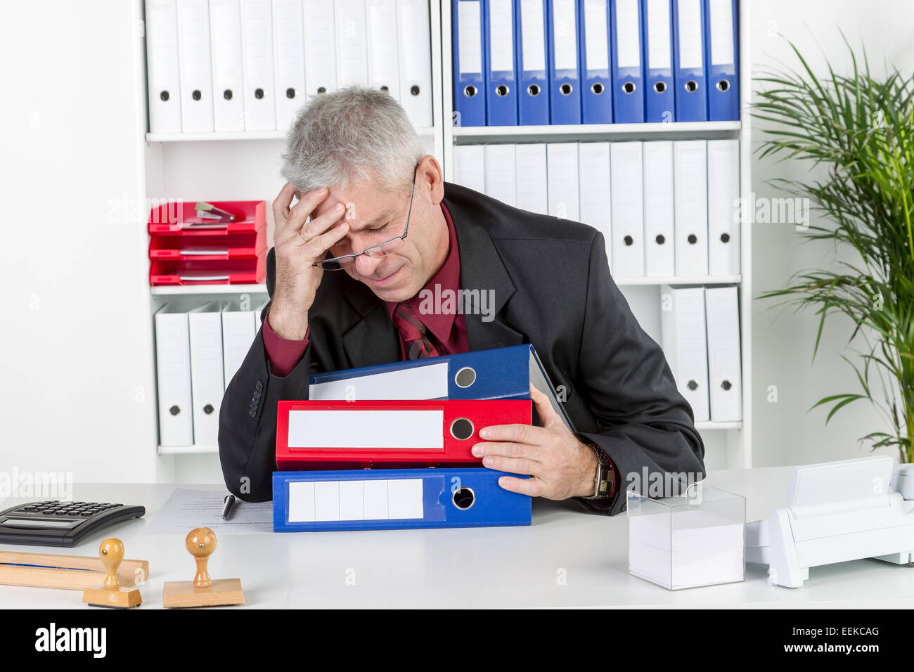 Mann mittleren Alters sitzt im Büro, hält sich den Kopf, hat Kopfschmerzen, Middle-aged man with a headache, - Stock Image