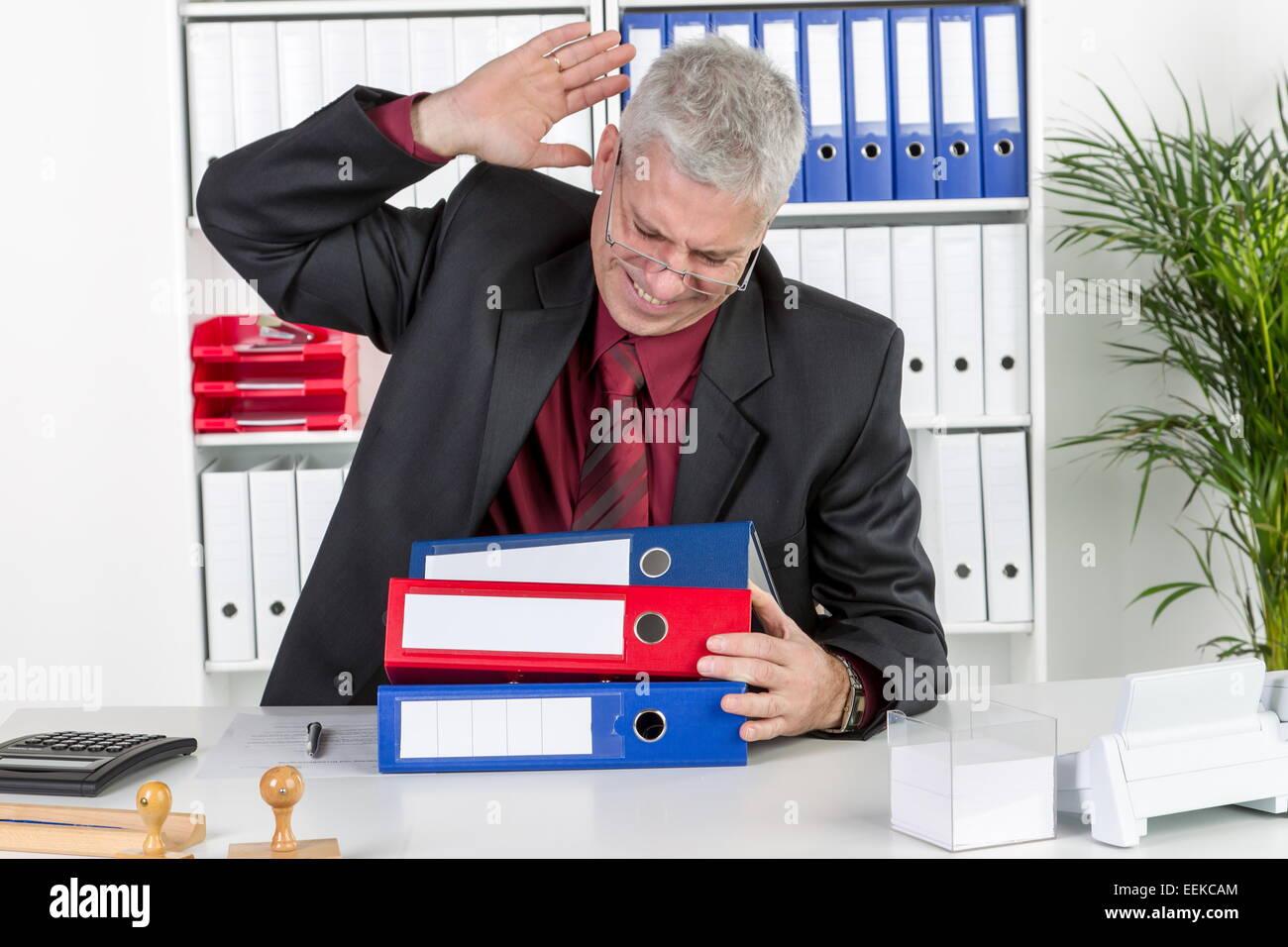Mann mittleren Alters sitzt im Büro, ärgert sich, ist überlastet, Middle-aged man, sitting in his - Stock Image