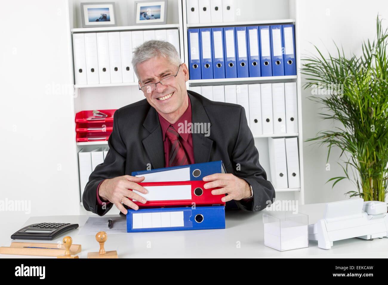 Mann mittleren Alters sitzt im Büro, ägert sich, ist überlastet, Middle-aged man, sitting in his - Stock Image