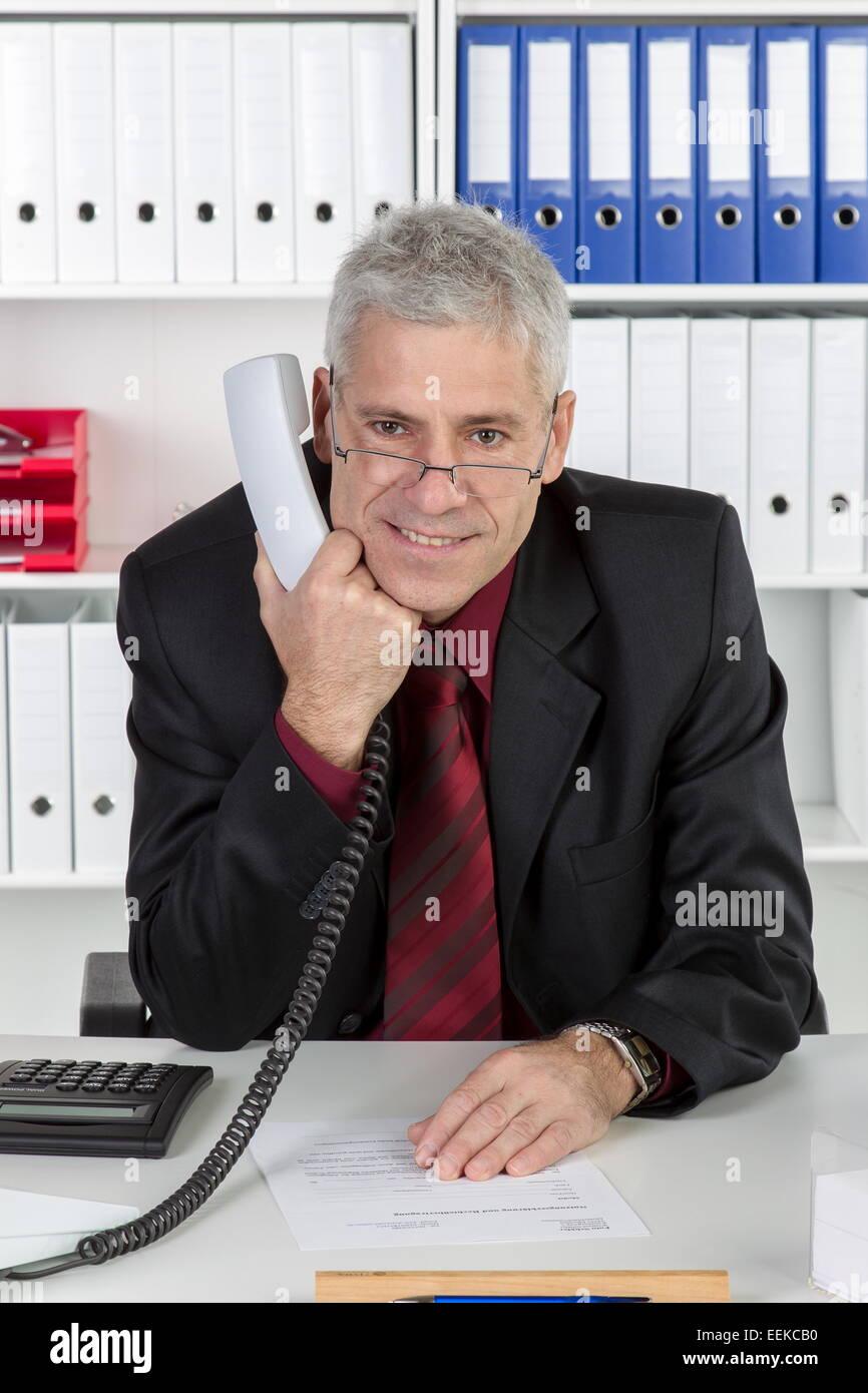 Mann mittleren Alters sitzt im Büro, Middle-aged man sitting in his office - Stock Image