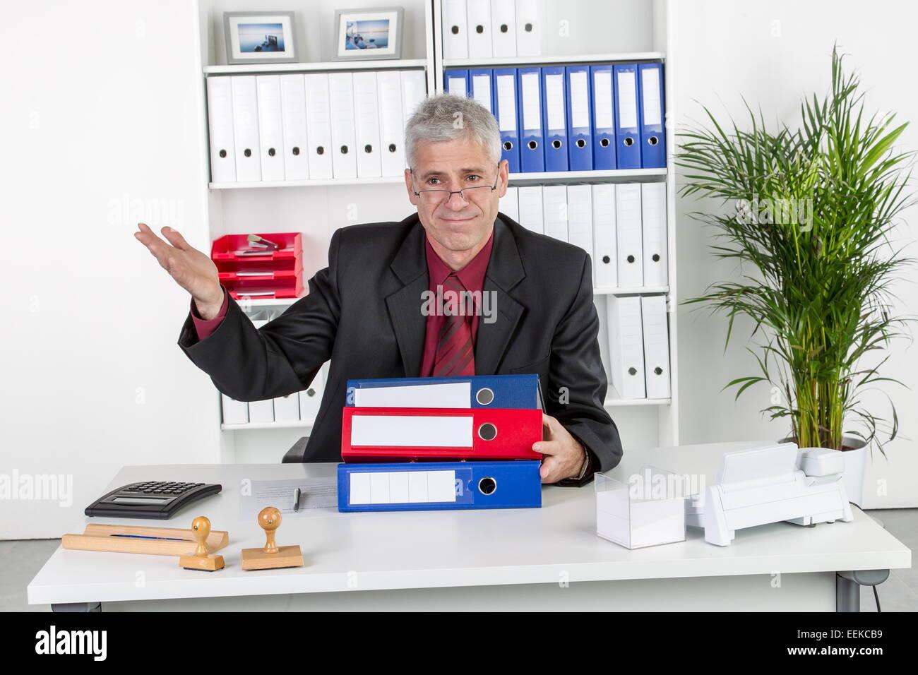 Mann mittleren Alters sitzt im Büro und gestikuliert, Middle-aged man, sitting in his office, gesticulating - Stock Image