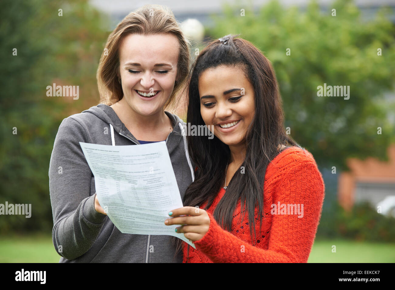 Two Female Students Celebrating Exam Results Together - Stock Image