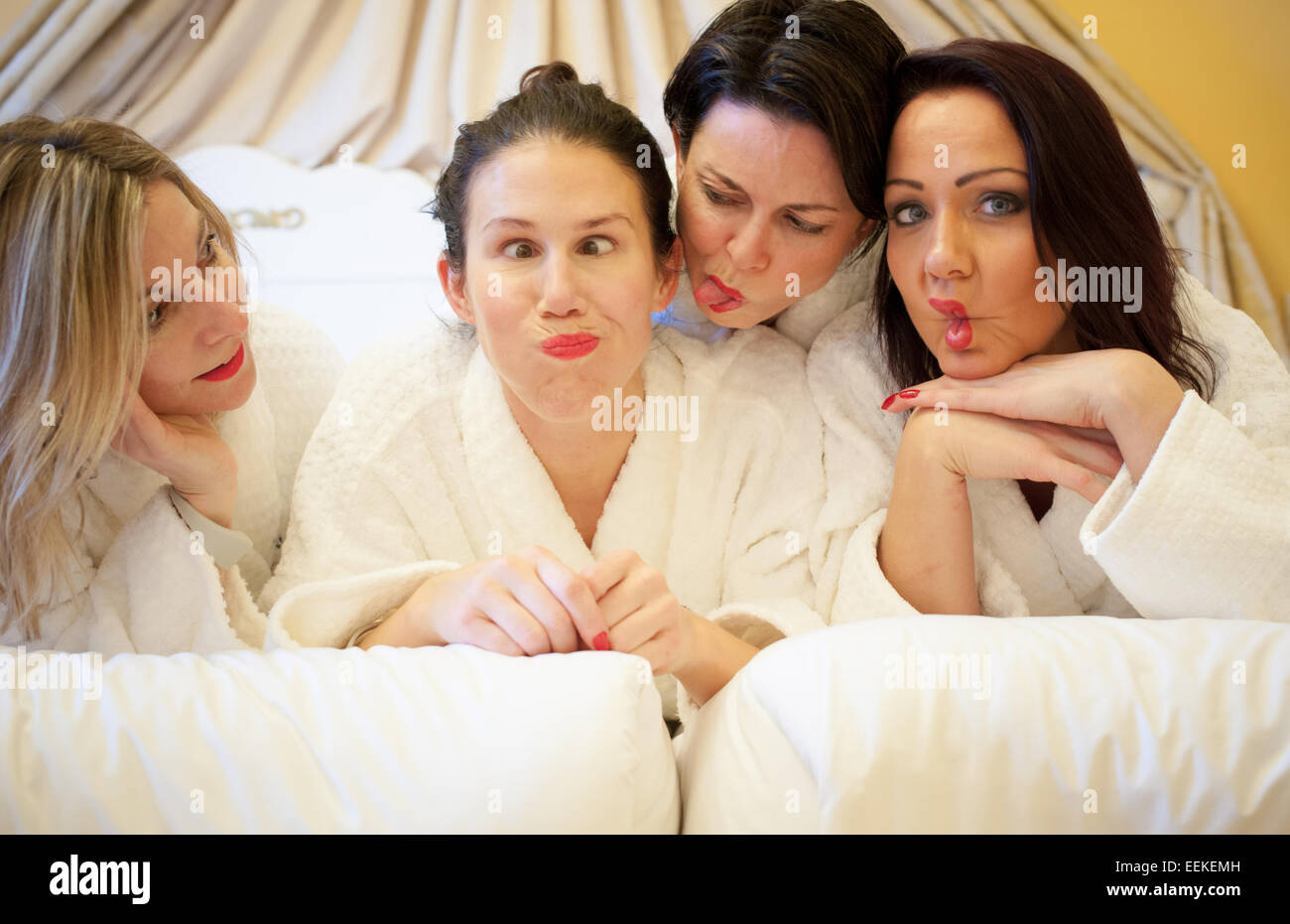 Group of attractive women in white robes in a luxury hotel messing about having fun on a health spa hen weekend Stock Photo