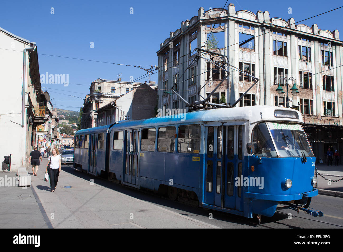 A tram on Mula Mustafe Bašeskije Street, in background a building damaged by bombs. Sarajevo, Bosnia-Herzegovina Stock Photo
