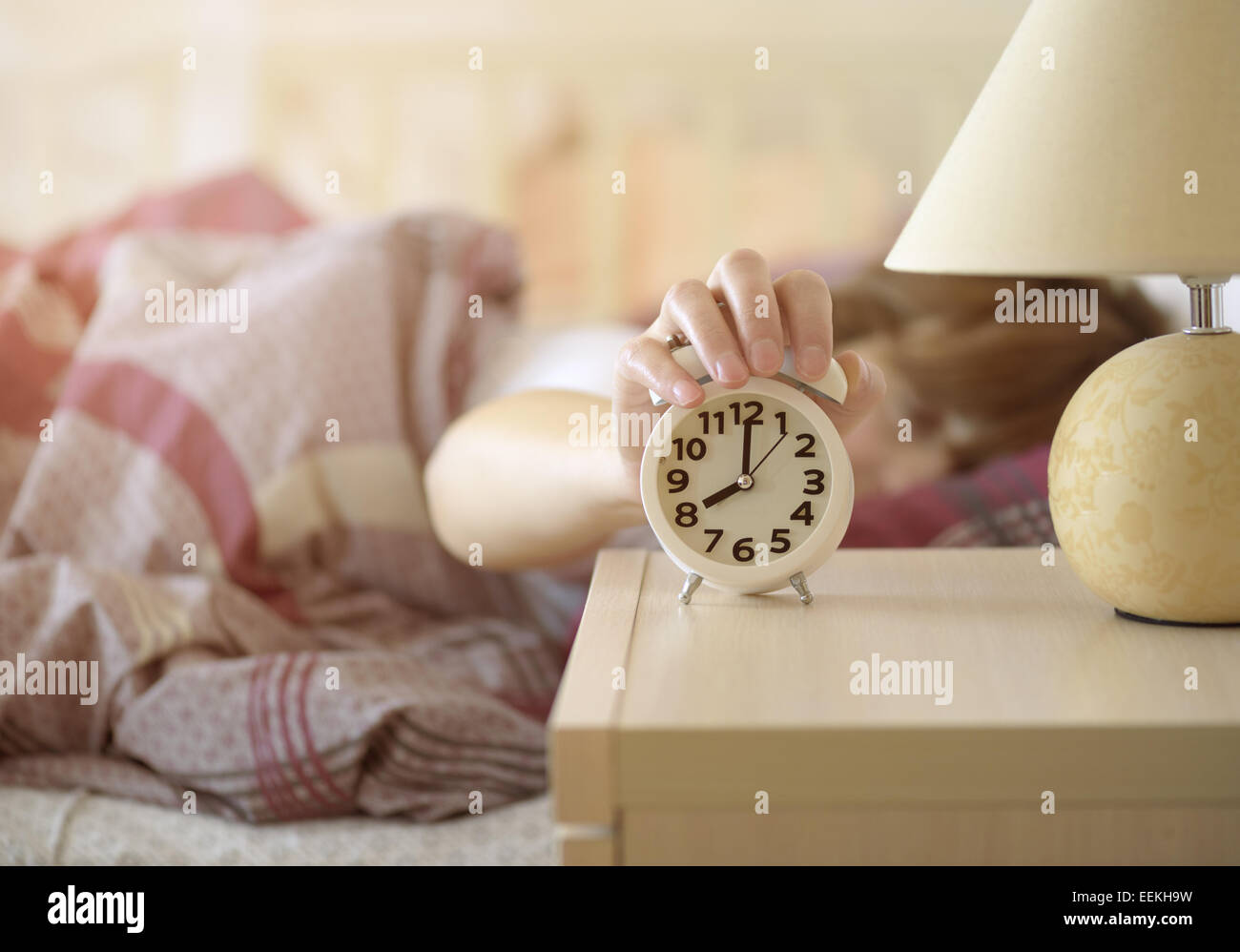girl turns off the alarm clock waking up in the morning from a call Stock Photo