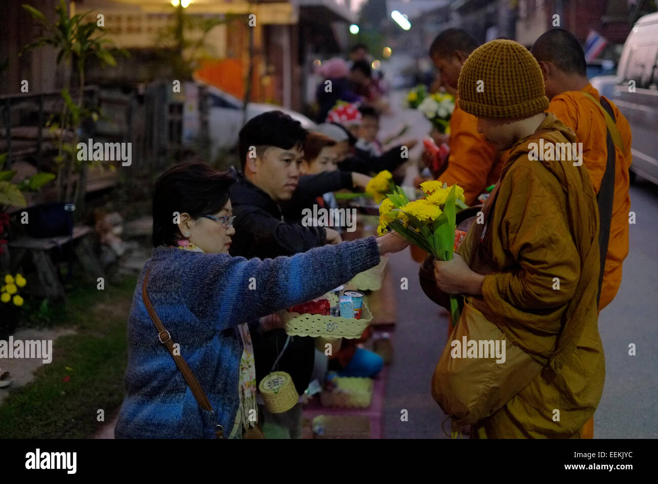 Buddhist monks receiving alms from local people before first light on Chaikhong street, which on weekend evenings Stock Photo