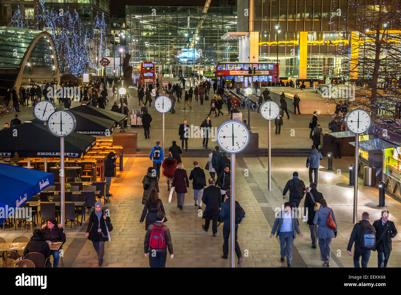 Canary Wharf showing commuters beneath six clocks showing the time as 6pm on a weekday winter evening - Stock Image