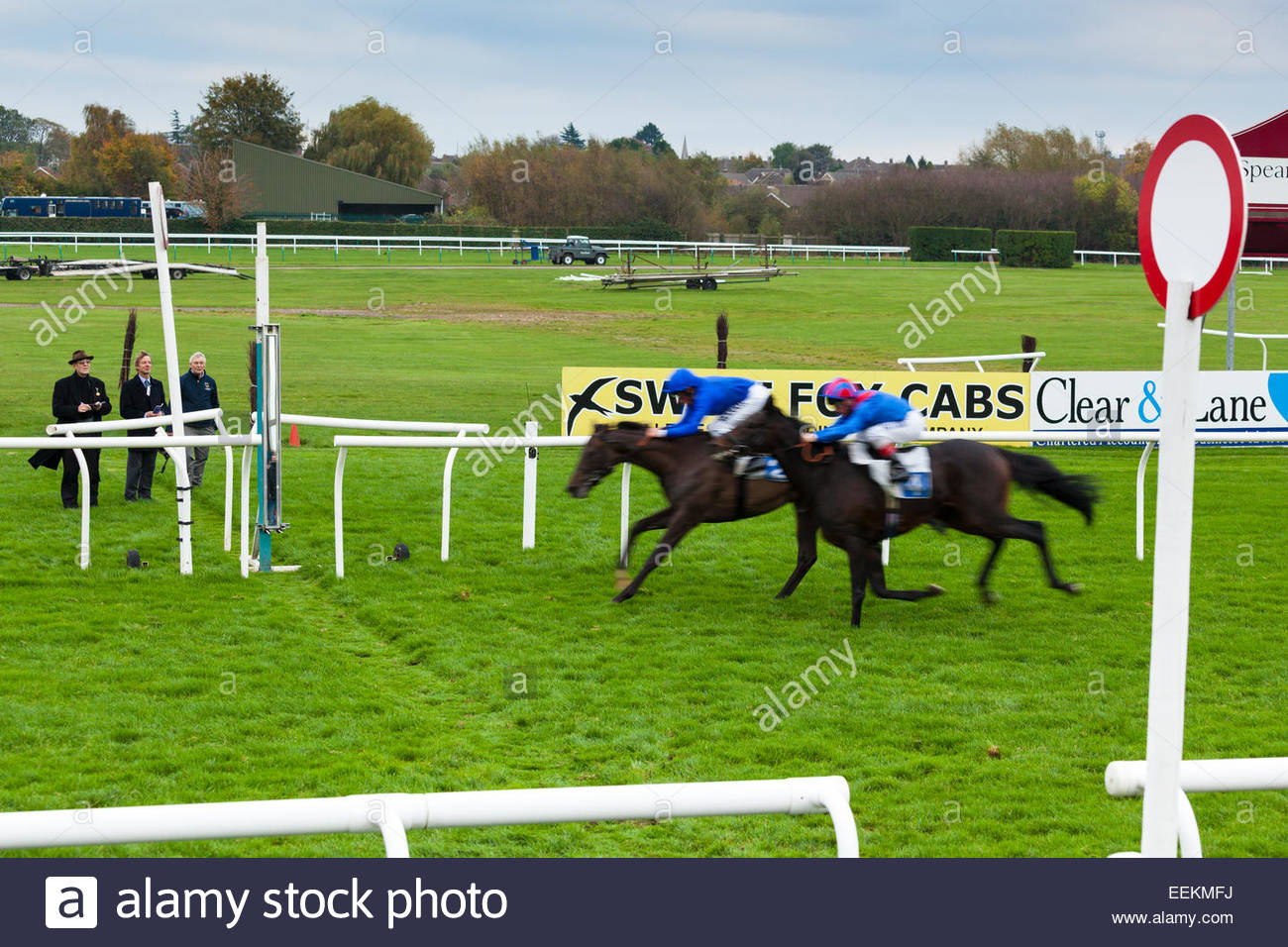 Tight finish as two horses and jockeys approach the finishing line at Leicester racecourse. 27 October 2014 Stock Photo
