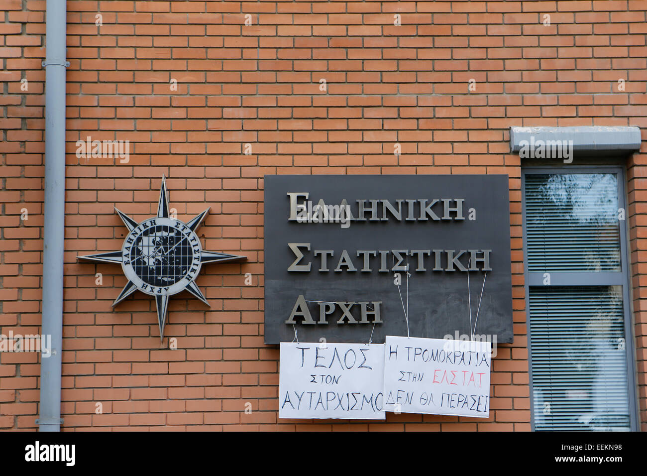 Protest posters hang on the official sign of the Hellenic Statistical Authority, reading 'End to Authoritarianism' - Stock Image