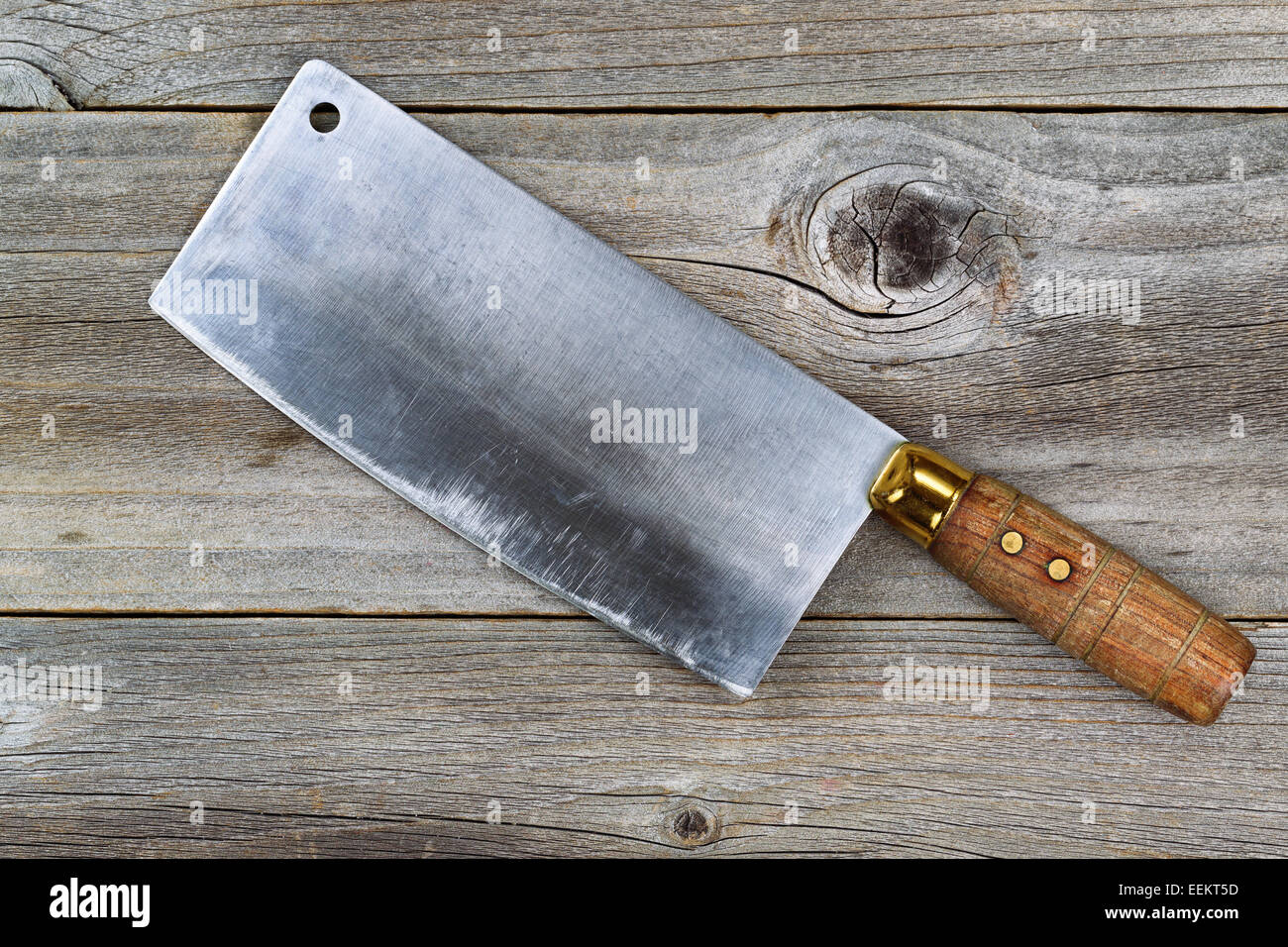 Close up of a large old traditional butcher knife on rustic wood - Stock Image